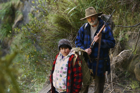 Picture of tall, older man and stout, younger boy staring at the camera. The younger boy is wearing a backpack, and the older man is holding a rifle. (Scene from Hunt for the Wilderpeople)